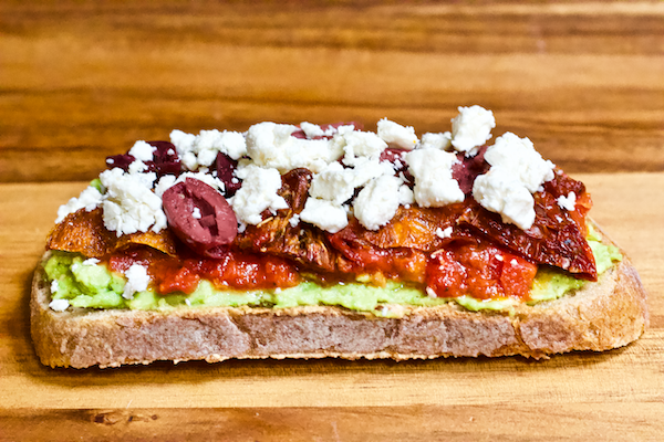 Healthy Avocado Toast - 2 Ways | Delicious, flavorful, and FRESH avocado toast made in two unique ways!  A Mediterranean inspired slice with olives, feta, & roasted red peppers and a sriracha & goat cheese variety with just the right amount of spice. You'll never be bored by avocado toast again!